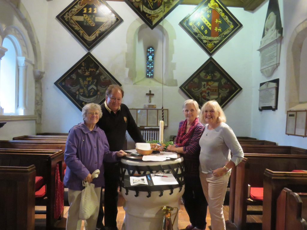 Visitors viewing the ancient font, possibly Anglo Saxon, at All Saints in Little Bookham